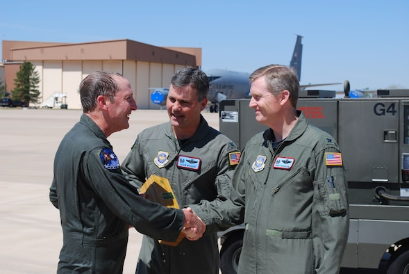 """Chief Master Sgt. John Waller, 137th Air Refueling Wing, receives a congratulation handshake from his commander Col. Gregory Fergusson after flying his """"fini flight"""" as an Oklahoma Air National Guard aircrew member. Also congratulating him is the 137th ARW Operations Group commander, Col. Devin Wooden. The chief's final flight marked several career milestones -- achieving more than 10,000 flying hours combined in the C-130 and KC-135R aircraft, being selected as the new 137th ARW Command Chief, and his 52nd birthday.   The Oklahoma-based unit was the first Air National Guard wing to become an associate wing to an Air Force Reserve Wing."""