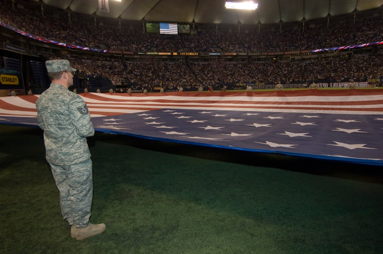 Technical Sgt. Tony Jones from the Joint Force Headquarters of the Minnesota National Guard holds a giant American flag for the national anthem at center field along with over two dozen other Airmen and Soldiers in the home opener for the Minnesota Twins on April 6, 2009. USAF Official Photo by Senior Master Sgt. Mark Moss
