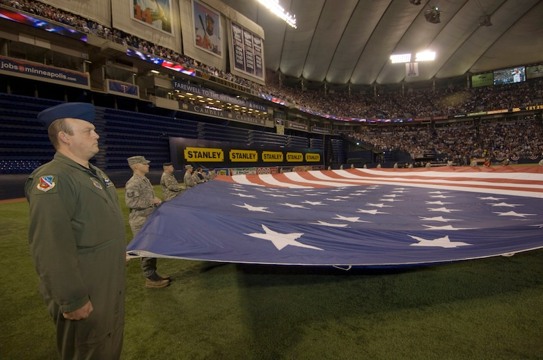 Master Sgt. Rick Krivanek (left) from the 109th Airlift Squadron anchors the upper left corner of the American flag held by Minnesota National Guard Airmen and Soldiers in the middle of the Hubert H. Humphrey Metrodome for the national anthem in the home opener for the Minnesota Twins on April 6, 2009. USAF Official Photo by Senior Master Sgt. Mark Moss