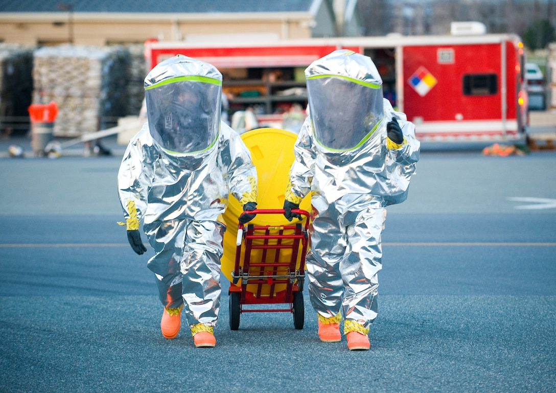 Two 436th Civil Engineer Squadron firefighters move a hazardous material spill kit during a Major Accident Response Exercise at Dover Air Force Base April 9. The Airmen practiced donning their Flash-Protected Level A suits during the MARE. In the event of a real-world emergency, the flash suits, coupled with other hazardous material gear, would keep them safe from hazardous chemical environments. (U.S. Air Force photo/Tom Randle)