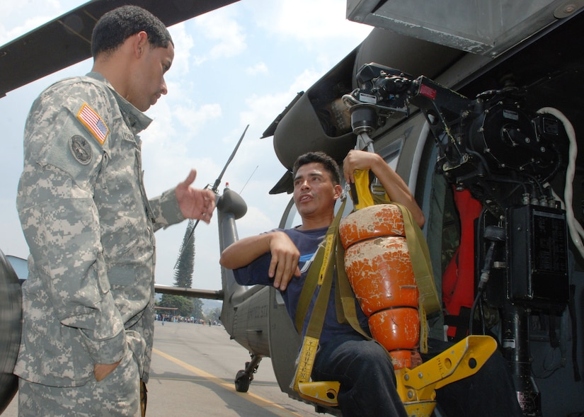 SOTO CANO AIR BASE, Honduras - Army Specialist Juan Perez-Fernanzez, 1-228th Aviation Regiment, shows Ever Aviles the hoist on a UH-60 Blackhawk helicopter during a Honduran air show in Tegucigalpa, April 14.  Specialist Perez-Fernandez is a Blackhawk flight engineer assigned to Joint Task Force-Bravo here.  The unit supported the airshow with a helicopter as a static display and a medical team.  (U.S. Air Force photo/Tech. Sgt. Rebecca Danét)