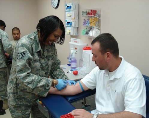 SHAW AIR FORCE BASE, S.C. - Staff Sgt. Wescott performs a phlebotomy procedure, a procedure more commonly known as 'drawing blood,' on Tech. Sgt. Bisignano for his annual PHA. This is the typical experience for most people who come to the lab. (U.S. Air Force photo/2nd Lt. Emily Chilson)