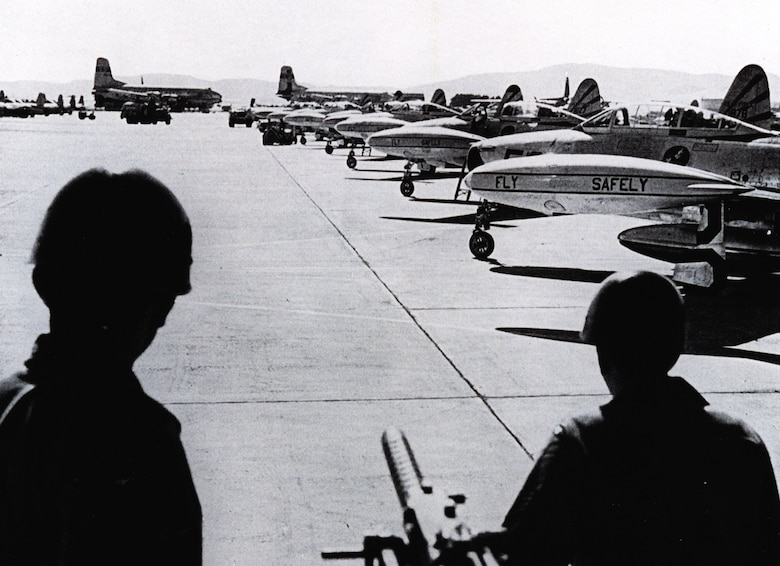 Two Air Policemen at Travis Air Force Base, Calif., monitor a flightline full of 31st Fighter Escort Wing F-84Gs prior to the fighters' launch for Hickam AFB, Territory of Hawaii, as part of Operation Fox Peter One.  The large transport aircraft in the background are Military Air Transport Service C-74 Globemasters, part of the support force. (U.S. Air Force historical photo)