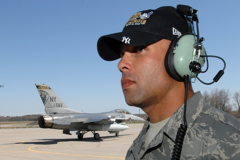 """The 174th Fighter Wing, Syracuse NY, F-16C Fighting Falcon depart Hancock Field Air National Guard Base to take part in the 2009 """"New"""" Yankee Stadium Opening Day Ceremonies. Staff Sgt. Preston Cox, 174 Fighter Wing Crew Chief watches the jets taxi out for their mission. (USAF Photo by: SSgt James N. Faso II)"""