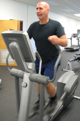 """Ken Hemshrot, NEADS Emergency Manager, works out on an elliptical machine at the Fitness Center. He was crowned the """"Biggest Loser"""" after dropping 51 pounds which represented a total percent weight loss of 20 percent (Photo by Maj. Leo Devine)."""