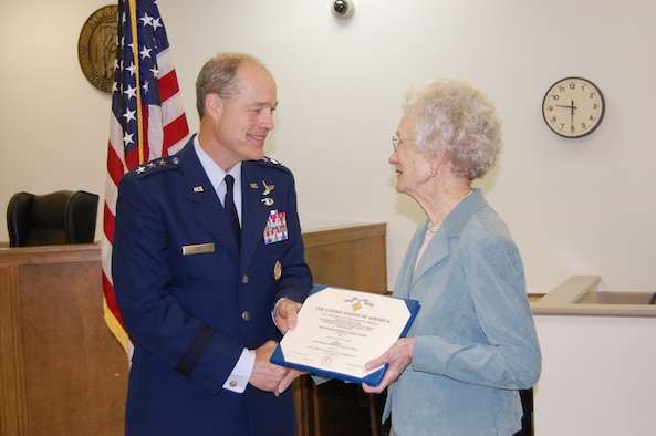 Lt. Gen. Allen Peck, Air University commander, presents Mrs. William (Doris) Norred with her late-husband's Distinguished Flying Cross with Valor on Monday. Capt. William Norred's military records were reviewed, and it was determined he earned the DFC on a combat mission during World War II. (Air Force photo by Carl Bergquist)