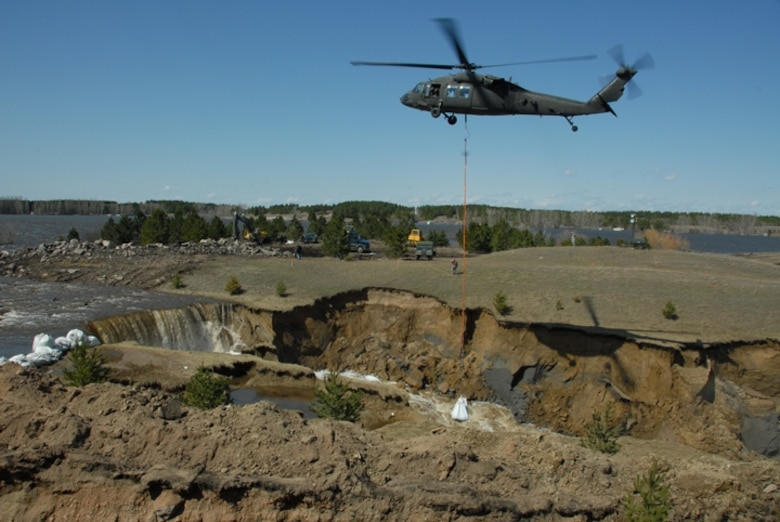 A North Dakota National Guard helicopter places 1-ton sandbags at the Cottonwood Creek Dam at Lake LaMoure on April 19, 2009.  The sandbags slowed the water flow from the eroded spillway.  Photo by SMSgt David Lipp, 119th Wing Public Affairs
