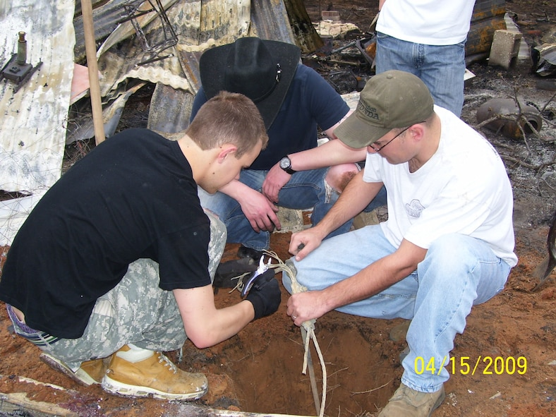 Airmen from the 552nd Training Squadron help clean up after a wildfire destroyed a local family's home.