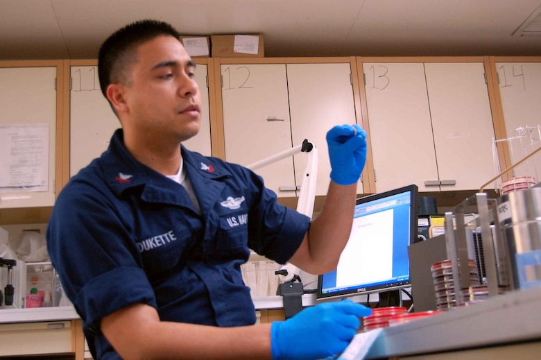 USNS COMFORT - Hospital Corpsman 2nd Class Philip Deukette, a laboratory technician aboard the hospital ship USNS Comfort, checks organism samples April 13 in the micro-biology section of the ship's medical laboratory.