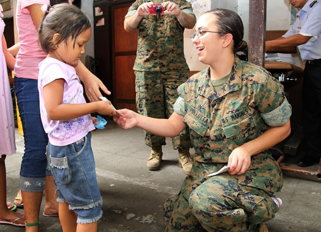U.S. Marine Lance Cpl. Alycia Pollotta, intelligence analyst, III Marine Expeditionary Force, hands a Balikatan 2009 sticker to a Philippine girl during a civic military operation at the Santo Nino Parish Church here April 22. AFP and U.S. forces handed out more than a ton of clothing, toys and shoes to 200 needy families in the area on behalf of Operation Good Will. (Photo by Lance Cpl Cristina Gil)