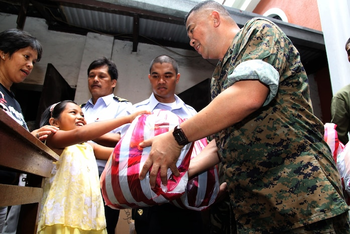 Hospital Corpsman 1st Class Eduardo Mojica, corpsman with 1st Marine Air Wing, hands a bag full of clothing and toys to a young Philippine girl on behalf of Operation Good Will during a civic military operation held in collaboration with Balikatan '09 at the Santo Nino Parish Church here April 22. More than 30 AFP and U.S. troops assisted with handing out over a ton of goods to needy Philiippine people in the area. (Photo by Lance Cpl Cristina Gil)