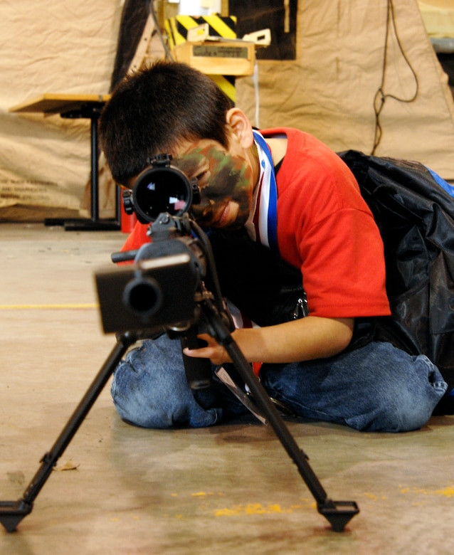 "WHITEMAN AIR FORCE BASE, Mo. - A young ""Airmen"" takes aim with a safed Barret M107 .50 caliber sniper rifle April 18 during Operation Spirit. ""Airmen"" were able to view several aspects of deployed locations. Operation Spirit is a simulated deployment line for school-aged kids that allows children to experience what their military parents go through during a deployment. The ""Airmen"" were accompanied by their parents and received goodies form several base agencies. (U.S. Air Force photo/Staff Sgt. Jason Barebo)"