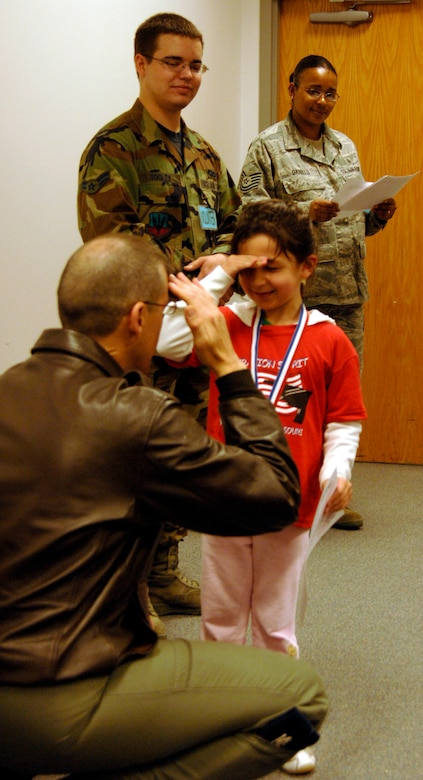 "WHITEMAN AIR FORCE BASE, Mo. - ""Airman"" Melody Mertes salutes Col. Thomas Bussiere, 509th Operations Group commander, April 18 during an awards ceremony at Operation Spirit. Operation Spirit is a simulated deployment line for school-aged kids that allows children to experience what their military parents go through during a deployment. The ""Airmen"" were accompanied by their parents and received goodies form several base agencies. (U.S. Air Force photo/Staff Sgt. Jason Barebo)"