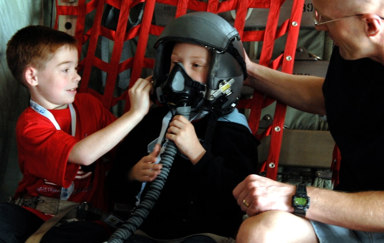 "WHITEMAN AIR FORCE BASE, Mo. - ""Airman"" Andrew Cizek tries on a pilot's helmet while on board a C-130 April 18 during Operation Spirit. Young ""Airmen"" were able to experience several aspects of deploying to help them better understand what their parents go through during a real-world deployment. Operation Spirit is a simulated deployment line for school-aged kids that allows children to experience what their military parents go through during a deployment. The ""Airmen"" were accompanied by their parents and received goodies form several base agencies. (U.S. Air Force photo/Staff Sgt. Jason Barebo)"