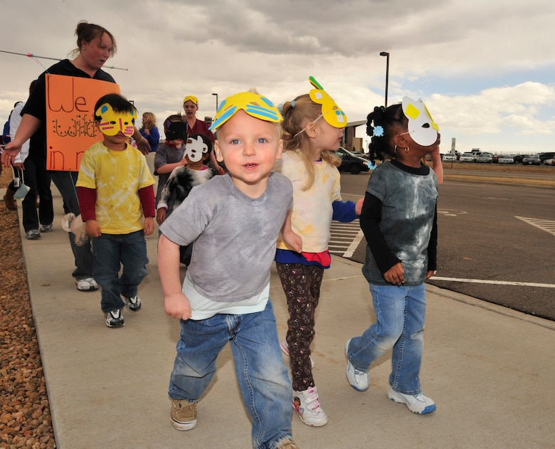 BUCKLEY AIR FORCE BASE, Colo. -- Children from the A Basin Child Development Center march in a parade to kickoff the Month of the Military Child here, April 3.  Children, parents and staff from both CDCs participated in the event.  Many of the children dressed up in masks, face paint and carried flags and streamers to walk in the parade.  The month of April is dedicated to the more than 1.7 million American children under the age of 18 that have at least one parent serving in the military.  (U.S. Air Force photo by Senior Airman Alex Gochnour)