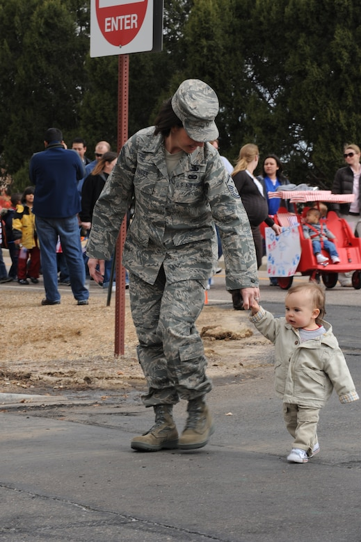 BUCKLEY AIR FORCE BASE, Colo. -- Master Sgt. Deanna Snider, 460th Mission Support Group first sergeant, holds the hand of her son, Avery, during a parade to kickoff the Month of the Military Child here, April 3.  Children, parents and staff from both CDCs participated in the event.  The month of April is dedicated to the more than 1.7 million American children under the age of 18 that have at least one parent serving in the military.  (U.S. Air Force photo by Senior Airman John Easterling)