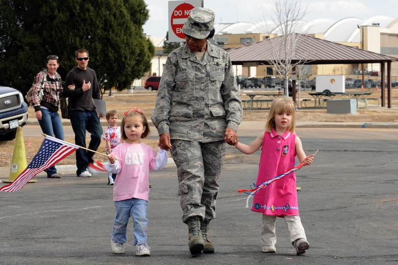BUCKLEY AIR FORCE BASE, Colo. -- Colonel Charlotte Wilson, 460th Space Wing Vice Commander, holds the hands of two children from the Crested Butte Child Development Center during a parade to kickoff the Month of the Military Child here, April 3.  Children, parents and staff from both CDCs participated in the event.  Many of the children dressed up in masks, face paint and carried flags and streamers to walk in the parade.  The month of April is dedicated to the more than 1.7 million American children under the age of 18 that have at least one parent serving in the military.  (U.S. Air Force photo by Senior Airman John Easterling)