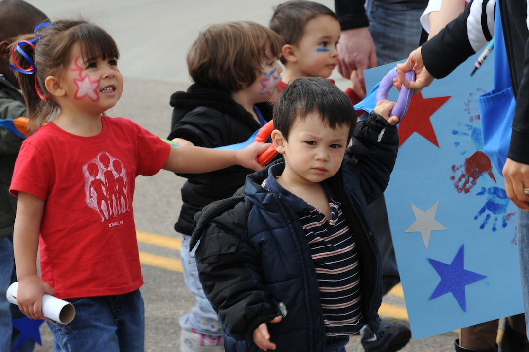 BUCKLEY AIR FORCE BASE, Colo. -- Children from the Crested Butte  Child Development Center participate in the kickoff parade for the Month of the Military Child here, April 3.  Children, parents and staff from both CDC? participated in the event.  Many of the children dressed up in masks and face paint to walk in the parade.  The month of April is dedicated to the more than 1.7 million American children under the age of 18 that have at least one parent serving in the military.  (U.S. Air Force photo by Senior Airman John Easterling)