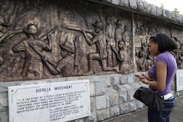 Lance Cpl. Tyrika Bradby, administrative clerk, III MEF, reads a placard of a mural commemorating the lives of Philippine service members who gave their lives on the island of Corregidor in World War II during an educational visit April 25. Several U.S. service members participating in Balikatan '09 spent the day learning about the earlier RP-U.S. history.