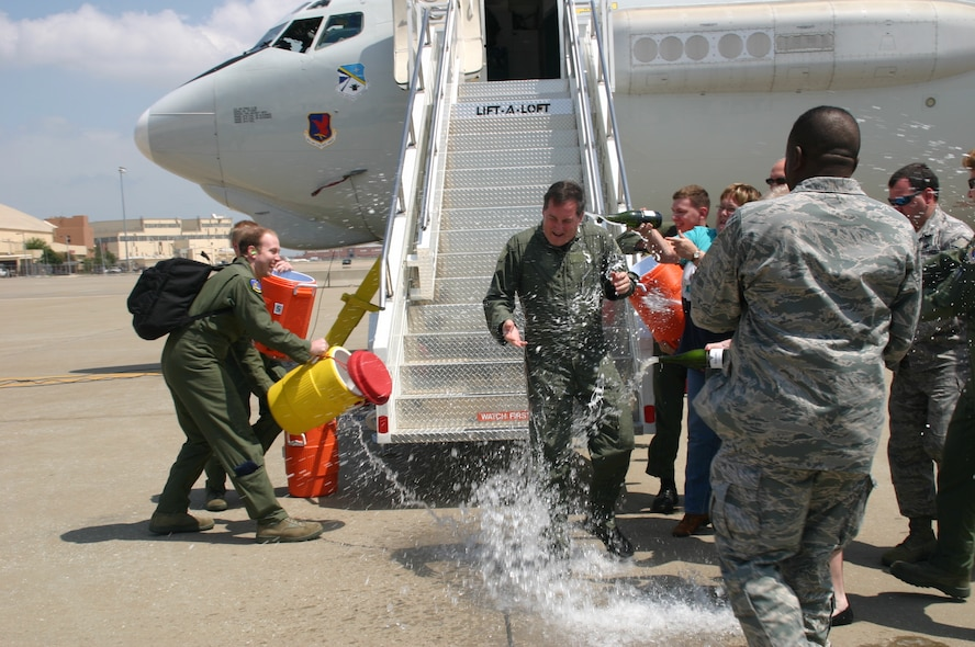 As Col. Joseph Rossacci, vice commander, 552nd Air Control Wing, stepped off the jet, he was soaked with champagne and water as part of the celebration of his final flight on the E-3 Sentry during his assignment here. (Air Force Photo by 1Lt Kinder Blacke)
