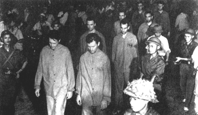 """Prisoners were paraded before angry crowds in Hanoi, where loudspeakers blared insults and encouraged the crowd's abuse. Many in the crowd attacked the POWs. Front row (l-r): Richard Kiern and Kile Berg; second row Robert Shumaker and """"Smitty"""" Harris; third row Ronald Byrne and Lawrence Guarino. (U.S. Air Force photo)"""