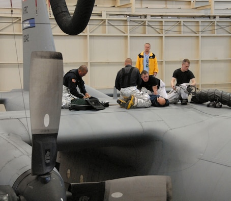 Members of the Maxwell Fire Department assist with the rescue of a 908th Airlift Wing aircraft maintenance member who passed out from fumes while inspecting the interior of a C-130 Hercules fuel tank. The scenario was part of the Maxwell-Gunter April base exercise. (U.S. Air Force photo by Jamie Pitcher)