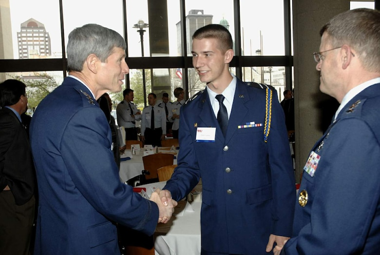 Gen. Norton Schwartz, Air Force chief of staff, congratulates University of Dayton Air Force ROTC Cadet 3rd Class Daniel Hughes on his decision to pursue a career as an Air Force officer, while Lt. Gen. Mark Shackelford, military deputy to the assistant secretary of the Air Force for acquisition, looks on. Generals Schwartz and Shackelford came to Dayton, Ohio, April 21 to congratulate and to challenge the Air Force acquisition workforce during DOD Acquisition Insight Days.  The event was organized by officials at Defense Acquisition University - Midwest Region and provided workshops, training and a forum for acquisition professionals to discuss ways to improve their processes.  (U.S. Air Force photo/Al Bright)