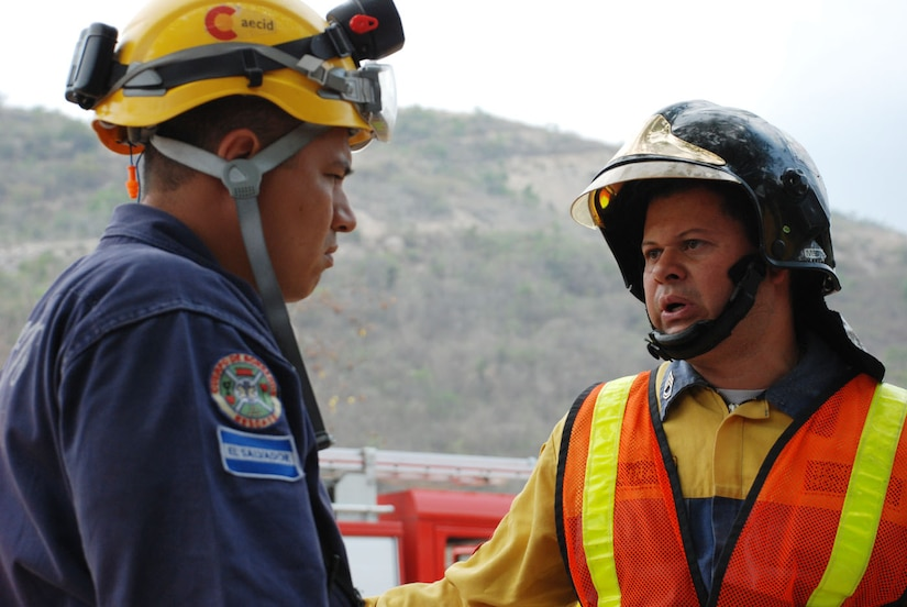 COMAYAGUA, Honduras - Sgt. Marlin Molina (right), a Honduran firefighter from Tegucigalpa, coordinates with a Salvadorian firefighter in response to a simulated explosion at La Farge Cement Factory here April 22.  Mr. Molina was the incident commander for the scenario, which was part of FA-HUM '09, a multinational disaster response exercise taking place in Honduras April 21-23.  (U.S. Air Force photo/Tech. Sgt. Rebecca Danét)