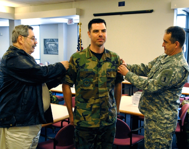 Tech. Sgt. Shannon Bond is awarded Master Sgt. stripes by Brigadier General Stephen Danner, Missouri adjutant general, and his father, George Bond, on 3 April, 2009. (U.S. Air Force photo by Master Sgt. Gregory Kunkle) (RELEASED)