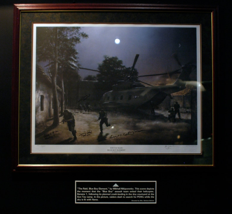 "DAYTON, Ohio - ""The Raid, Blue Boy Element,"" by Mikhail Nikiporenko. This scene depicts the moment that the ""Blue Boy"" assault team exited their helicopter, Banana 1, following its planned crash-landing in the tiny courtyard at the Son Tay camp. In the picture, raiders dash to search for POWs while the sky is lit with flares.This framed lithograph is on display in the Return with Honor: American Prisoners of War in Southeast Asia exhibit in the Southeast Asia War Gallery at the National Museum of the U.S. Air Force. (U.S. Air Force photo)"