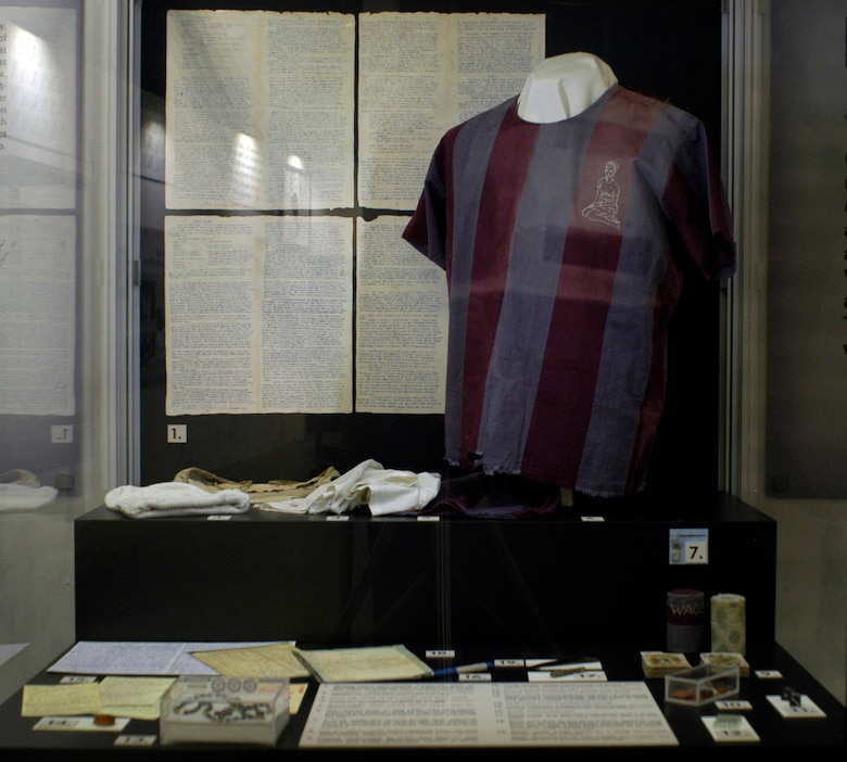 """DAYTON, Ohio - In this display is a handmade """"ditty bag"""" made from old undershirts, two needles and thread that a POW made from electrical wire by grinding them to proper size and shape on concrete and sharpening a nail to a point and using it as a punch for the eyes, a shirt issued prior to mid-1968 with the embroidery done in August 1972 by Capt. Edward Mechenbier of Dayton from a photo of his wife (he made his needles and thread from copper wire and an old blanket), metal repair tongs made by a POW for pulling straps through sandals, a skull cap made of two socks sent from home, undershorts mailed to a POW by his wife, who embroidered the hearts, in November 1969, a rosary made from bread colored with ink and string taken from a cotton blanket, pencil made of bread and cloth rolled over a toothpaste tube  with the lead was made of charcoal and soap, playing cards used by Capt. Tom Moe to play solitaire and bridge, dice made of bread dough, ashes and toothpaste, a North Vietnamese pen, a ring made from a toothbrush handle, a pinball game received in a parcel from home, the """"Acey Deucy"""" game pieces made of bread, ashes, and Kool-Aid received in a parcel from home, parts of Shakespeare's plays printed by a POW on toilet paper, poetry on cigarette wrappers, a book made in Hoa Lo for language classes and cigarette cases. These artifacts are part of the Return with Honor: American Prisoners of War in Southeast Asia exhibit in the Southeast Asia War Gallery at the National Museum of the U.S. Air Force. (U.S. Air Force photo)"""
