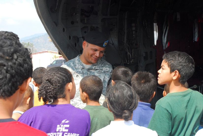 LA PAZ, Honduras - U.S. Army Sgt. Joselito Vicenty talks to local children as they look at a CH-47 Chinook helicopter here April 22. Sergeant Vicenty and 10 other U.S. servicemembers were in La Paz, participating in Fuerzas Aliadas Humanitarias, or FA-HUM '09 -- a multinational exercise designed to test emergency response capabilities during multiple simulated disaster situations. (U.S. Air Force photo/Tech. Sgt. Mike Hammond)