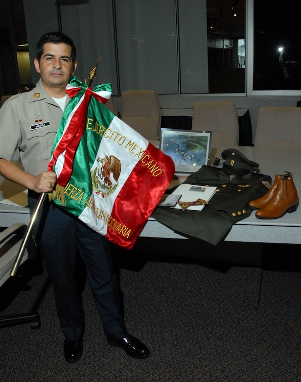 """DAYTON, Ohio - Mexican air force Lt. Col. Daniel Mojica stands in front of items while holding the unit colors for the Mexican Expeditionary Air Force (""""Fuerza Aérea Expedicionaria Mexicana"""" or FAEM). These items were donated during a ceremony at the National Museum of the U.S. Air Force. (U.S. Air Force photo)"""