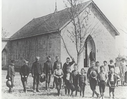 ST. MARY'S CHURCH.  The Post Chaplain, standing in the church doorway, was responsible for conducting educational classes for children on post.  Classes were held at the chapel-today's St. Mary's Chapel-and usually taught by the chaplain or one of his assistants.  Pictures here is a group of school children on recess from their studies.