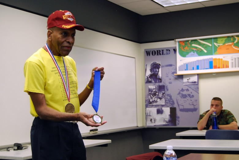 Dr. Granville Coggs shows off a gold medal he won for the 400-meter run during the 2009 San Antonio Senior Games during a World War II history class at the U.S. Air Force Academy, Colo., April 24. Dr. Coggs, one of the original Tuskegee Airmen, also wore the Congressional Gold Medal bestowed to all Tuskegee Airmen in a March 2007 ceremony. (U.S. Air Force photo/Staff Sgt. Don Branum)