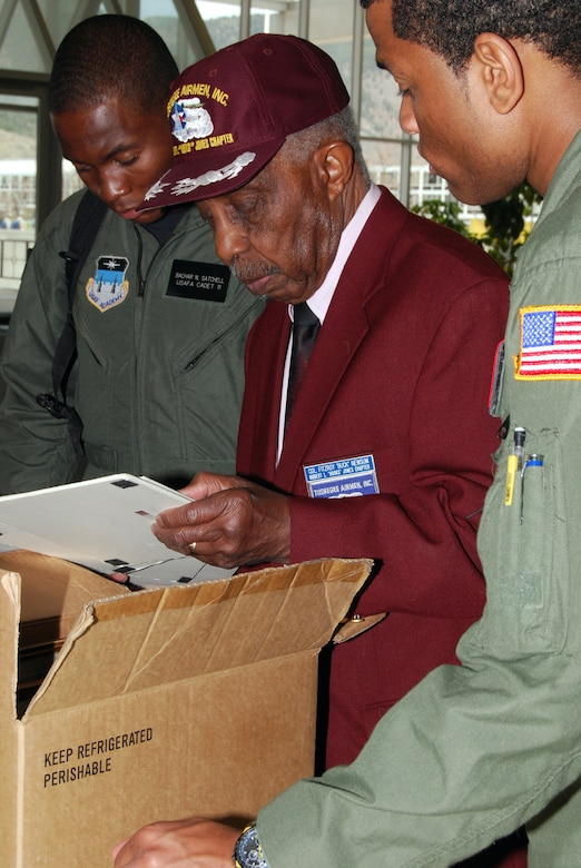 "Retired Col. Fitzroy ""Buck"" Newsum shows Tuskegee Airmen memorabilia to Cadets 3rd Class Bachar Satchell and Kyle Foley during a visit to the U.S. Air Force Academy, Colo., April 24. Mr. Newsum, one of the original Tuskegee Airmen, served under Brig. Gen. Benjamin O. Davis Sr. and then-Col. Benjamin O. Davis Jr. He was assigned to the 617th Bombardment Group during World War II. (U.S. Air Force photo/Staff Sgt. Don Branum)"
