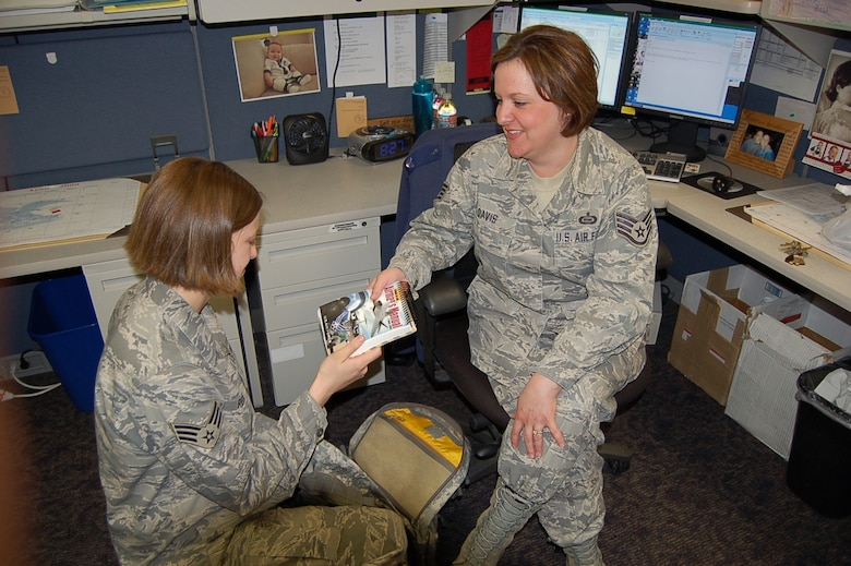BUCKLEY AIR FORCE BASE, Colo. -- Staff Sgt. Linda Davis(right) ensures an Airman is ready for deployment with an Airmans Manual.  Sergeant Davis, Unit Deployment Manager for the 566th Intelligence Squadron, is Team Buckley's Warrior of the Week for May 1-7.  She hails from Sacramento, Calif. (Courtesy photo)