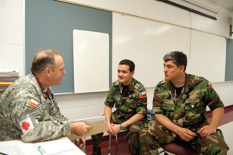 Chilean Military Air Force Lt. Col. Alger Rodo, a specialist in colorectal surgery, and Maj. Raul Berrios, a thoracic surgeon discuss with State Guard Capt. Wood, medical brigade, triage procedures at Pharr-San Juan-Alamo High School. The surgeons participate in an international exchange program between the State of Texas and the Republic of Chile during Operation Lone Star held at Pharr, Texas, July 29, 2009. (U.S. Air Force photo by Senior Master Sgt. Elizabeth Gilbert)