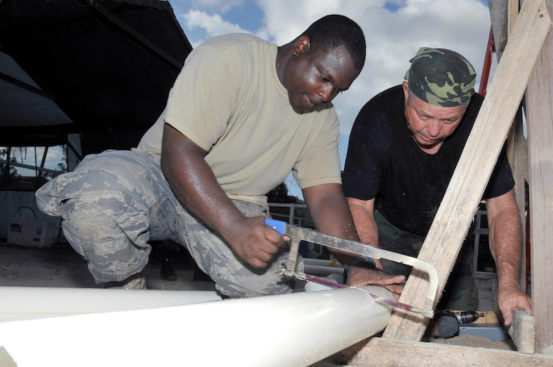 Tech Sgt. Ray Ball, heating, ventilating, and air conditioning craftsman, and Master Sgt. Victor Price, a engineering craftsman, both from the 301st Civil Engineer Squadron, Naval Air Station Joint Reserve Base Fort Worth, Texas, cut a piece of pipe for the new gutters at Timehri Nursery school July 29, 2009 in Georgetown, Guyana. Sergeant Ball, and Sergeant Rice are finishing up the renovation of the school. (U.S. Air Force photo by Airman 1st Class Perry Aston) (Released)