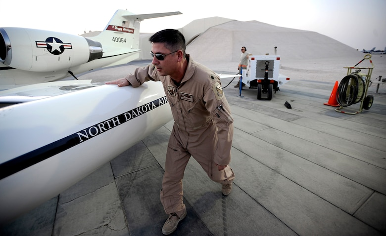 Lt. Col. Rick Omang, a C-21 pilot assigned to the 379th Expeditionary Operations Group, conducts a pre-flight inspection prior to conducting combat operations over Southwest Asia July 26. The C-21 is a twin turbofan engine aircraft used for cargo and passenger airlift. Colonel Omang is deployed from the 177th Airlift Squadron, North Dakota Air National Guard. (U.S. Air Force photo by Staff Sgt. Shawn Weismiller)