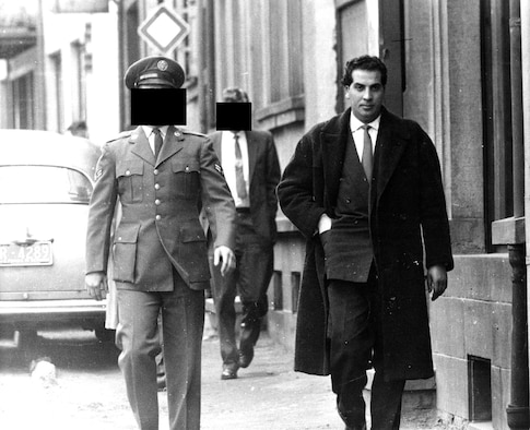 This is a terrorist being watched during the Cold War. The man on the right is an Algerian who claimed to be a member of the Front de la Libération Nationale, or FLN. When he attempted to buy machine guns and pistols from the Airman on the left, near Ramstein Air Base, Germany, in 1959, the Airman alerted OSI. Their meeting was recorded and photographed in an investigation in which OSI cooperated with French and German police. The man in the background is an OSI agent. (U.S. Air Force photo)