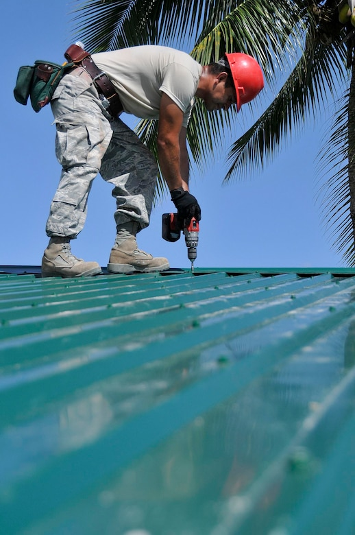 Staff Sgt. Joel Herrera-Ramos, a structural craftsman with the 555th Red Horse Squadron, from Nellis Air Force Base, Nev., installs a metal roof on the Bel-Air School in Georgetown, Guyana, on July 21, 2009. U.S. airmen are deployed to build the school as part of New Horizons Guyana. (U.S. Air Force photo by Airman 1st Class Perry Aston) (Released)