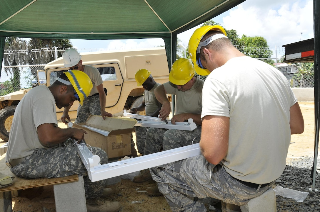 Soldiers from the 878th Engineer Battalion, Georgia Army National Guard, build light fixtures for the new clinic July 3, 2009 in Georgetown, Guyana. Soldiers from the Georgia Army National Guard are building the $350,000 clinic, which will feature four examination rooms, an office, waiting room and bathroom. (U.S. Air Force photo by Airman 1st Class Perry Aston) (Released)