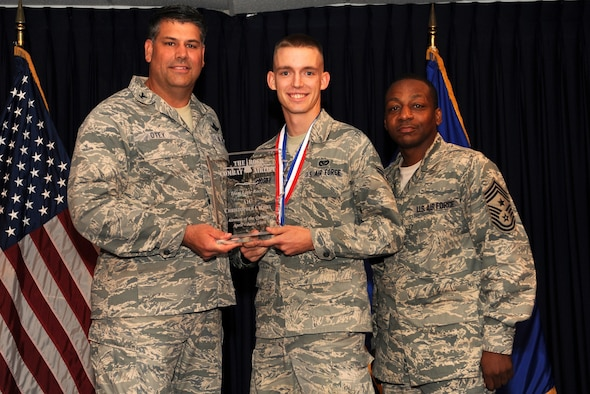 Col. Greg Otey, 19th Airlift Wing commander, and Chief Master Sgt. Anthony Brinkley, 19th Airlift Wing command chief, presents  Airman 1st Class Christopher Crosby, 19th Civil Engineer Squadron, a quarterly award for Airman of the quarter at Little Rock Air Force Base, Ark. July 30. (U. S. Air Force photo by Senior Airman Jim Araos)