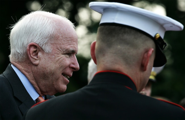 Arizona Senator John McCain is escorted to his seat during the weekly Marine Corps Sunset parade at the Marine Corps War Memorial Aug. 3. McCain is a long time friend and commrad of the nights guest of honor and Medal of Honor recipient retired Air Force Col. George 'Bud' Day. The two Vietnam veterans shared a prison sell as prisoners of war in 1967, during which they were tortured by Viet Cong forces. Day has remained a political ally over the years.