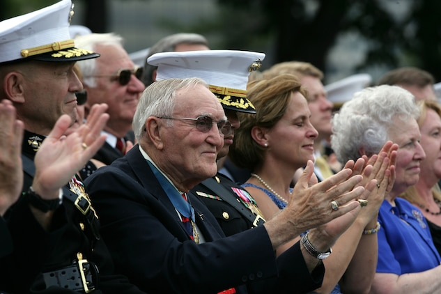 Retired Air Force Col. George 'Bud' Day, Medal of Honor recipient, applauds during the Silent Drill Platoon's performance at the weekly Marine Corps Sunset parade Aug. 3. Day was the night's guest of honor. He has served in three different military services, including the Marine Corps, during three different wars and is America's most decorated living military officer.  During his time as an Air Force pilot in Vietnam, Day was captured by North Vietnam forces. During his captivity he escaped, becoming the only prisoner of war to do so, but after two weeks of evasion, he was recaptured by Viet Cong forces. He was finally released in 1973.