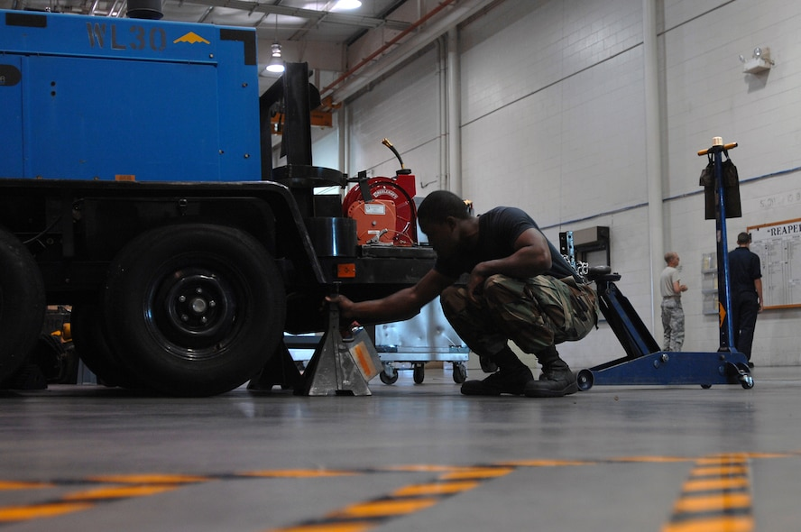 WHITEMAN AIR FORCE BASE, Mo. - Senior Airman Quintellis Darden, 509th Maintenance Squadron Aerospace Ground Equipment Mechanic, puts a floor jack in place before performing maintenance on a diesel welder. AGE mechanics perform anywhere between 40 to 60 hours of maintenance a week in support of the B-2 mission. (U.S. Air Force photo/Senior Airman Kenny Holston)