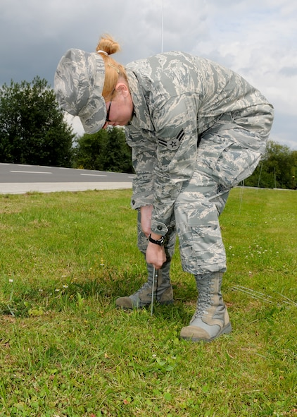 SPANGDAHLEM AIR BASE, Germany -- Airman 1st Class Christina Peabody, 52nd Medical Operations Squadron, prepares a cordon near the 81st Fighter Squadron Aug. 3 on Spangdahlem AB. The cordon was established to designate the boundaries of a simulated tactical area of responsibility for the upcoming Phase II exercise. The exercise will take place Aug. 4-7 in preparation for the 52nd FW's NATO Tactical Evaluation next summer. (U.S. Air Force photo by Airman 1st Class Nathanael Callon)