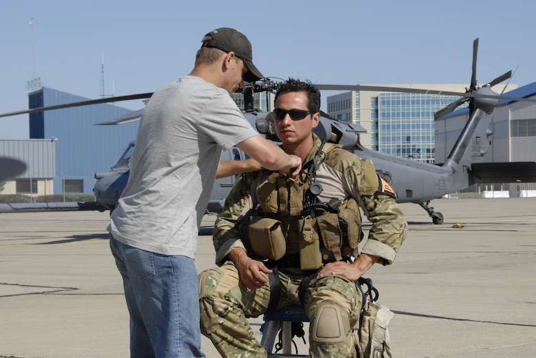 Tech. Sgt. Mike Davis, photographer for the Air National Guard Advertising and Marketing Creative Branch, puts a lapel microphone on Tech. Sgt. Luigge Romanillo, a pararescueman from the 131st Rescue Squadron, in preparation for an interview at Moffett Federal Airfield, Calif., with the Air National Guard Advertising and Marketing team during a video shoot for the redesign of GoANG.com, Aug. 5, 2009.  (Air National Guard photo by Tech. Sgt. Ray Aquino)