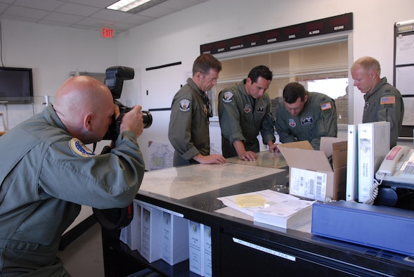 Master Sgt. Scott Reed, combat photographer for the Air Force Recruiting Service, documents pararescuemen from the 131st Rescue Squadron as they coordinate their drop location on a map at Moffett Federal Airfield, Calif., Aug. 4, 2009.  Sergeant Reed worked with the Air National Guard Advertising and Marketing team during a video shoot for the redesign of GoANG.com. (Air National Guard photo by Tech. Sgt. Ray Aquino)